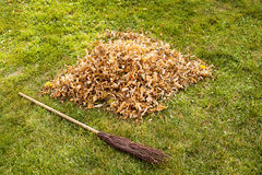 Autumn clearing - besom and a pile of leaves Royalty Free Stock Photo