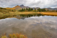 Autumn clouds. Small fine and smooth lake in the Swiss Alpes, reflecting mountains royalty free stock photos