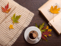 Autumn coffee and book. Cup of coffee, book, autumn leaves ans wool scarf on table stock photography
