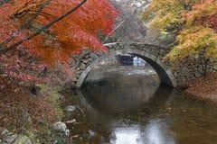Autumn color and old stone arched bridge at Namsangol traditional folk village, Seoul, South Korea - NOVEMBER 2013 Stock Image