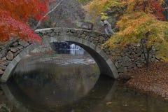 Autumn color and old stone arched bridge at Namsangol traditional folk village, Seoul, South Korea - NOVEMBER 2013 Royalty Free Stock Photo