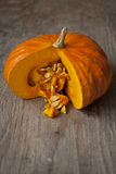 Autumn colored pumpkin exposing seeds. Orange ripe pumpkin with cutted section exposing fresh pulp and seeds. The pumpkin is on rustic wooden table. Shallow Stock Photo