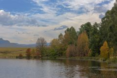 Autumn colored trees next to the water. Drakensberg South Africa royalty free stock photos