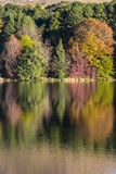 Autumn colored trees reflection on water. Drakensberg South Africa Stock Photo