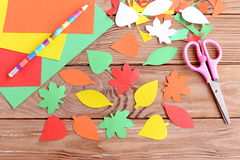 Autumn colorful leaves cut from paper, pencil, scissors, colored paper sheets on a wooden background. Teaching scissor cutting Royalty Free Stock Photos