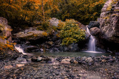 Autumn. The colors crossed by a quiet stream Royalty Free Stock Photo