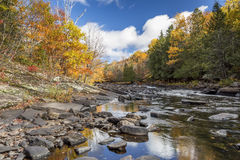 Autumn Colors Lining a Rock-strewn River Stock Photo
