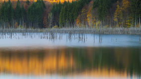 Autumn colors reflect in the waters of a mountain lake Stock Image