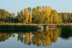 Autumn Colors Reflected on a Lake. With a Fishing Dock Royalty Free Stock Photos