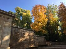 Autumn coloured trees beyond the steps to Alhambra. With a massive stone-wall at the forefront royalty free stock photos