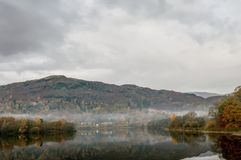 Autumn colours at Grasmere. Still water on Grasmere with reflections of Autumn colours and a small landing jetty in the foreground Stock Photos