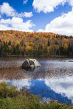 Autumn colours by the lake and the mountains. Picture taken in the wilderness depicting the Autumn season on the eastern part of Canada (Quebec).  The season is Stock Image