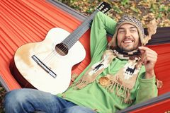 Autumn is coming Young handsome man with guitar relaxs in a hammock outdoor. He smiles and looks on an oak leaf in his hand. Fall Royalty Free Stock Photo