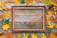 Bright autumn leaves and picture frame on wooden background with copy space. mock up for text, congratulations, phrases, lettering. Autumn composition. bright Royalty Free Stock Photo