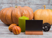 Autumn composition with candle and blackboard on a light wooden background Royalty Free Stock Image