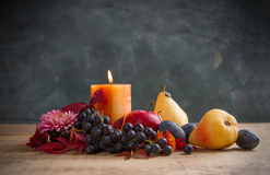 Autumn composition with candle, flowers and fruit Royalty Free Stock Photo