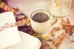 Autumn composition. Cup of coffee, blanket, autumn leaves, cinnamon sticks on beige background royalty free stock photos