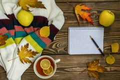 Autumn composition. Cup of tea, apple, dried autumn leaves, beige sweater on wood background. royalty free stock photo