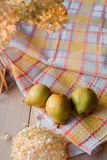 Autumn composition. Dried hydrangea, pears on a linen napkin. On a wooden background. Royalty Free Stock Photo