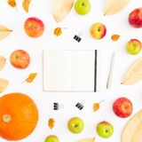 Autumn composition of fall leaves, apples and pumpkin with notebook, pen and clips on white background. Thanksgiving day. Flat lay. Autumn composition of fall royalty free stock photos