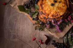 Autumn composition from flowers, berries and yellow cake Stock Photos