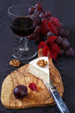 Autumn composition: grapes, scarlet leaves, piece of cheese and Royalty Free Stock Images