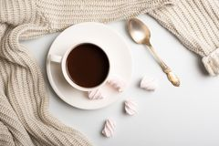Autumn composition. Hot chocolate, warm wool sweater and marshmallows on a white background. flat lay, top view.