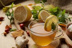 Autumn composition with hot tea with ginger and lemon on a natural wooden table. stock image