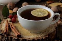 Autumn composition with hot tea cinnamon, dog rose, nuts on a brown wooden table stock photos