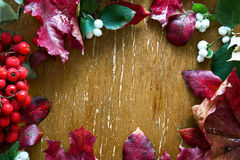 Autumn composition of leaves, flowers, berries on wooden background. Royalty Free Stock Photo