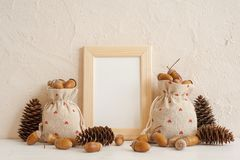 Autumn composition with mock up frame, acorns in linen bags and pine cones. Autumn, fall concept. Copy space. royalty free stock photos