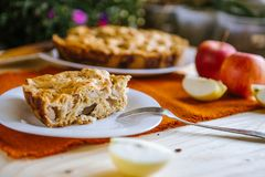 Autumn composition: Pie with apples, coffee and notepad. Dry leaves on a wooden table. stock image
