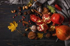 Autumn composition. Pomegranate with nuts, spices and dry leaves on a dark wooden table. Top view. Copy space royalty free stock images