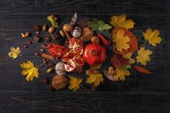 Autumn composition. Pomegranate with nuts, spices and dry leaves on a dark wooden table. Top view. Copy space royalty free stock photography