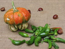 Autumn composition with pumpkin, green peppers and chestnuts on jute fabric background Stock Photo