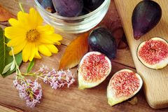Autumn composition - ripe figs and flowers. Ripe sweet figs . Healthy mediterranean fig fruit . Stock Photos