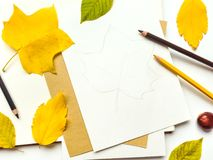 Autumn composition with sketchbook and pencils, decorated with yellow and green leaves. Flat lay, top view Royalty Free Stock Image