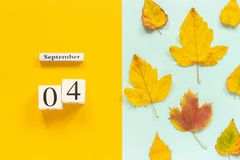 Autumn composition. Wooden calendar September 4 and yellow autumn leaves on yellow blue background. Top view Flat lay. Mockup Concept Hello September stock images