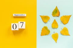 Autumn composition. Wooden calendar September 7 and yellow autumn leaves on yellow blue background. Top view Flat lay. Mockup Concept Hello September stock images