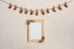 Autumn composition with wooden frame. Acorn with clothespins on clothes line rope. Wooden pegs. Flat lay, top view, copy space. royalty free stock image