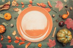 Autumn composition, yellow leaves, small pumpkins lined around brown plate, space for text flat lay royalty free stock images