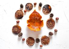 Autumn concept, abstract background. Some dried slices of orange, hazelnuts and a bowl in a maple leaf shape on white background,wallpaper for a web site and stock photography