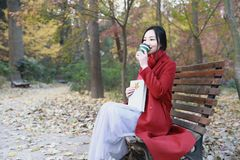 Anonymous woman enjoying takeaway coffee cup on sunny cold fall day sit on bench stock images