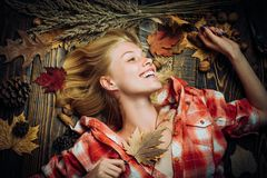 Autumn concept. Attractive woman wearing in fashionable seasonal clothes having Autumnal mood. Autumn discounts. Sweet. Young woman playing with leaves, looks stock image