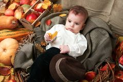 Autumn concept - child boy lie on yellow leaves with fruits and vegatbles, red apples and pumpkins royalty free stock photography