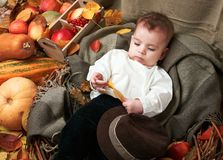 Autumn concept - child boy lie on yellow leaves with fruits and vegatbles, red apples and pumpkins stock images