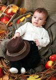 Autumn concept - child boy lie on yellow leaves with fruits and vegatbles, red apples and pumpkins stock photos
