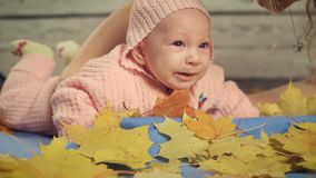 Newborn baby girl lying on carpet and autumn leaves stock video