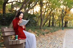 Young asian sensual woman reading a book in romantic autumn scenery.Portrait of pretty young girl in autumnal forest Stock Photo