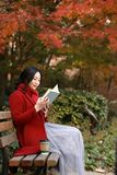 Young asian sensual woman reading a book in romantic autumn scenery.Portrait of pretty young girl in autumnal forest Royalty Free Stock Photography